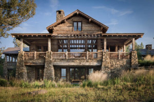 Mountain lodge style home with reclaimed timbers and Montana Moss Rock and native landscaping.