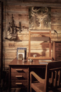 Fishing cabin design with hewn timbers and antique furniture.